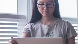 Image of young woman using her tablet at home